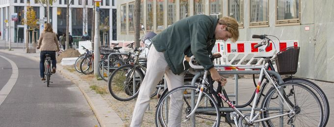 Mann schließt Rad an Fahrradbügel an