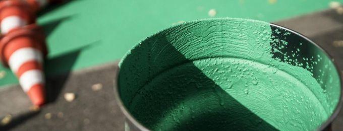 Farbeimer mit verkehrsgrüner Farbe für Beschichtung von Radweg
